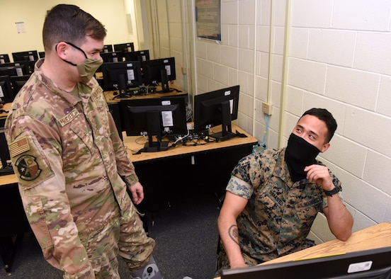 U.S. Air Force Staff Sgt. Jonathan Preiser, 316th Training Squadron instructor, engages with Marine Corps Staff Sgt. Terry Summerfield, Marine Corps Detachment student, during the in-classroom portion of the Apprentice Electronic Signals Intelligence Analyst (1N2A) course inside Fred Sebers Hall on Goodfellow Air Force Base, Texas, April 20, 2020. The classroom complied with the 17th Training Wing and federal safety regulations during the COVID-19 pandemic and shifted two-thirds of its material to digital. (U.S. Air Force Photo by Airman 1st Class Abbey Rieves)