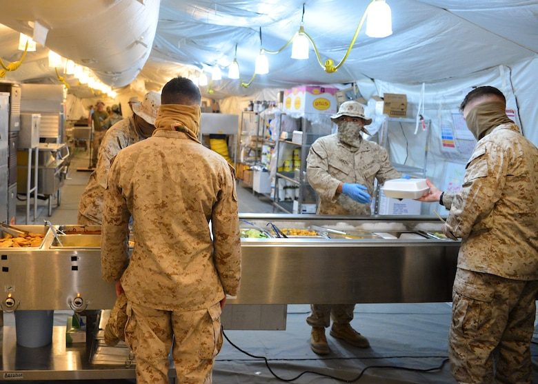 U.S. Marines serve patrons food as volunteers at the Sandstorm field kitchen, Ahmed Al Jaber Air Base, Kuwait, April 17, 2020. The 407th Air Expeditionary Group stood up the Sandstorm as a way to balance health protection levels and further support installation inhabitants by providing an additional avenue for customers to have a meal. (U.S. Air Force photo by Senior Airman Isaiah J. Soliz)