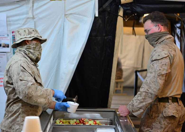 A U.S. Marine Corps volunteer prepares a meal for a fellow Marine at the Sandstorm field kitchen, Ahmed Al Jaber Air Base, Kuwait, April 17, 2020. The Sandstorm was stood up in an effort to further adhere to health protection levels by providing an additional avenue for customers to have a meal. (U.S. Air Force photo by Senior Airman Isaiah J. Soliz)