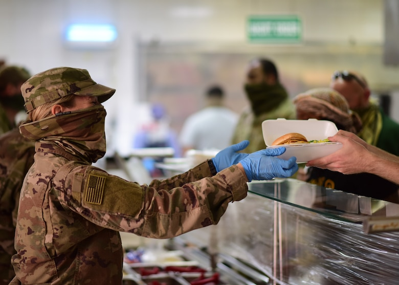 A volunteer from the U.S. Army Task Force Spartan hands a patron their meal at the Desert Winds Dining Facility, Ali Al Salem Air Base, Kuwait, April 16, 2020. Volunteers from across the installation have stepped up to help ensure the DFAC continues to remain open by promoting and enforcing heightened health protection guidelines. (U.S. Air Force photo by Senior Airman Isaiah J. Soliz)
