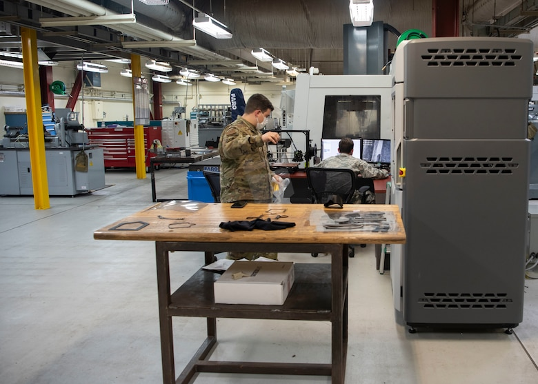 U.S. Air Force Staff Sgt. Adrian Gonzalez and Airman 1st Class Cyrus Bartony, from the 18th Equipment Maintenance Squadron, work together to 3D print a face shield April 9, 2020, at Kadena Air Base, Japan. Gonzalez and Bartony are the 3D print programmers that helped design the models to print personal protective equipment during COVID-19.