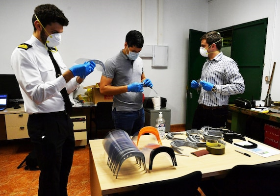 Miguel Angel Garcia (left), a Spanish Armada functionary; Milton Perez-Cruz (center), a mechanical engineer from Naval Surface Warfare Center Carderock Division; and David Sanchez, a Spanish Armada engineer, assemble face shields produced in their additive manufacturing lab at the Forward Deployed Regional Maintenance Center Detachment Rota, Spain, in April 2020 for use at local hospitals during the COVID-19 pandemic.