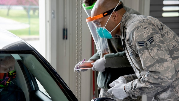 A black soldier wearing a mask and medical mask over his nose and mouth and white gloves talks to a man also wearing a mask sitting in a car.