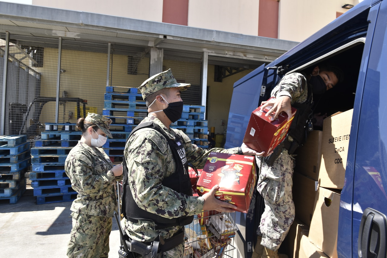 Sailors in uniform, all wearing face masks, load boxes into a van.