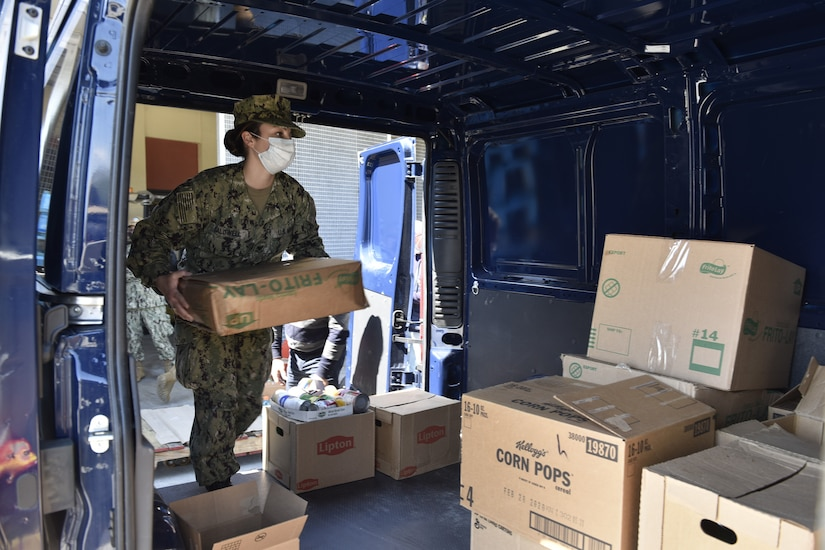 A sailor in uniform and wearing a face mask loads a box into the back of a van.
