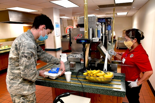 Airman 1st Class Logan Parent, 388th Aircraft Maintenance Squadron, pays for a meal with Angie Skeen, Hillcrest Dining Facility food services, at the Hill Air Force Base, Utah, April 23, 2020. The food services contractor, Native Resource Development Company, Inc., is continuing to provide carry out meals for the base's Airmen during the COVID-19 pandemic while keeping the dining facility extra clean and sanitized. (U.S. Air Force photo by Todd Cromar)