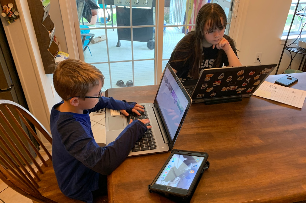 Two children sit at a kitchen table and operate laptop computers.