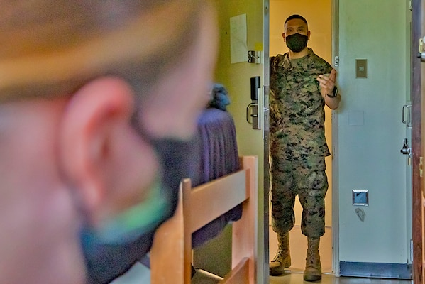 A Marine does a room check on one of his fellow Marines.