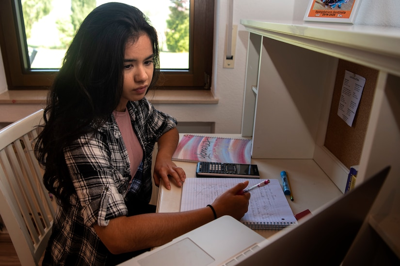A young lady holds pen to paper as she looks at a computer screen.