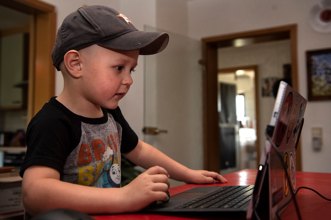 A small boy wearing a baseball cap and Thomas the Tank Engine T-shirt looks at a computer screen.