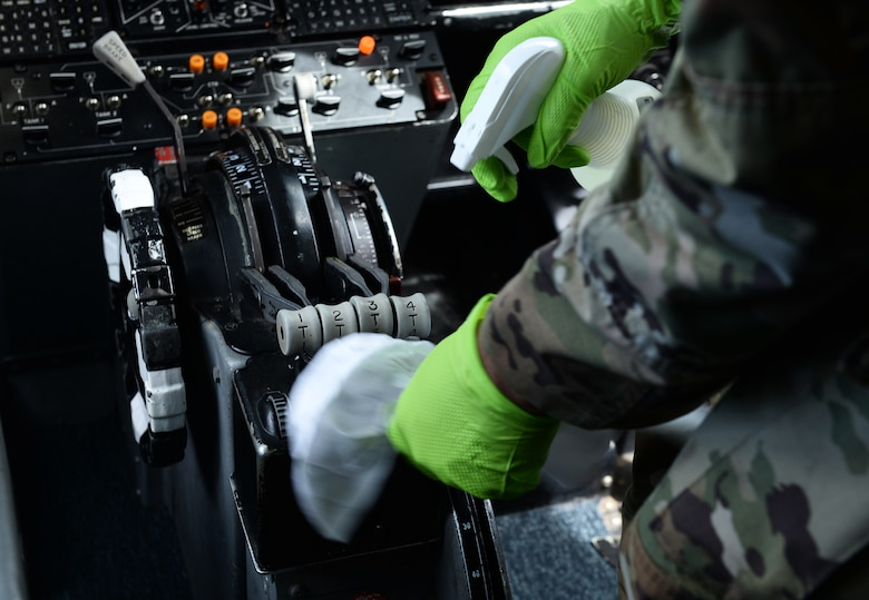 Airman disinfects throttle inside aircraft.