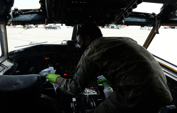 Airman disinfects cockpit of aircraft.