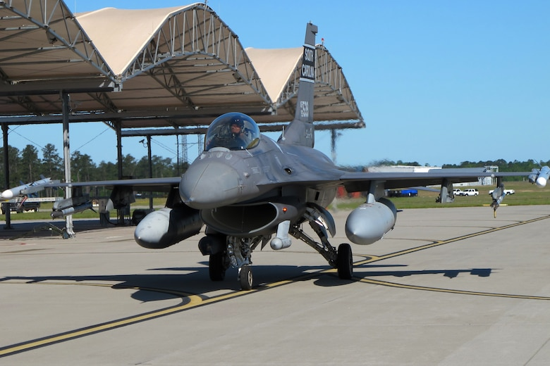 An F-16 fighter jet taxis under a blue sky toward the runway for takeoff.
