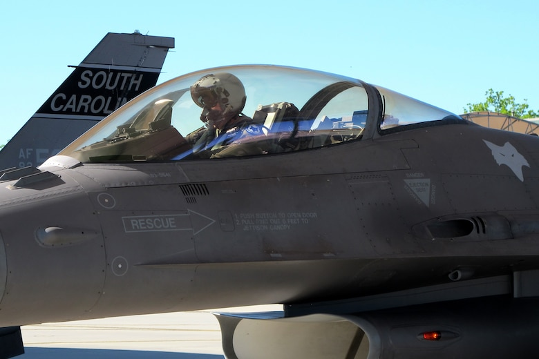 An F-16 pilot prepares for takeoff at under a bright blue sky and bright sun.