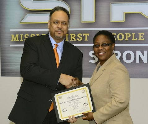 Dr. Charles Brandon, Director, Army Office of Business Transformation Process Improvement Program, awards Carolyn Harris, Huntsville Center's Program Improvement Manager, her Lean Six Sigma Master Black belt certificate in December. Harris is one of six MBBs in the U.S. Army Corps of Engineers.