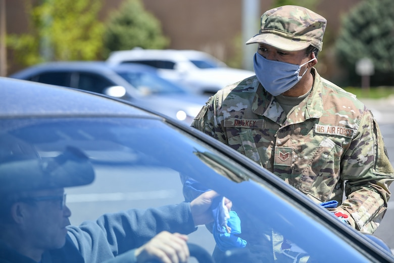Staff. Sgt. Nicklas Mulkey, 75th Air Base Wing, hands out cloth masks to military and civilian Airmen April 28, 2020, at Hill Air Force Base, Utah. Around 4,000 masks, most donated from nearby communities and also from the 531st Armament Textile Shop, were given out to Team Hill to keep safe and healthy during the COVID-19 pandemic. (U.S. Air Force photo by Cynthia Griggs)