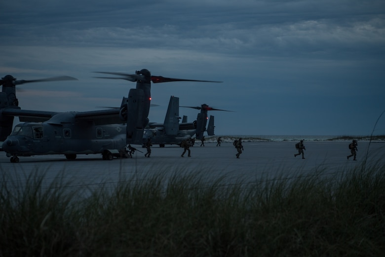 rotary aircraft sit on a landing zone with airmen walking out onto a beach