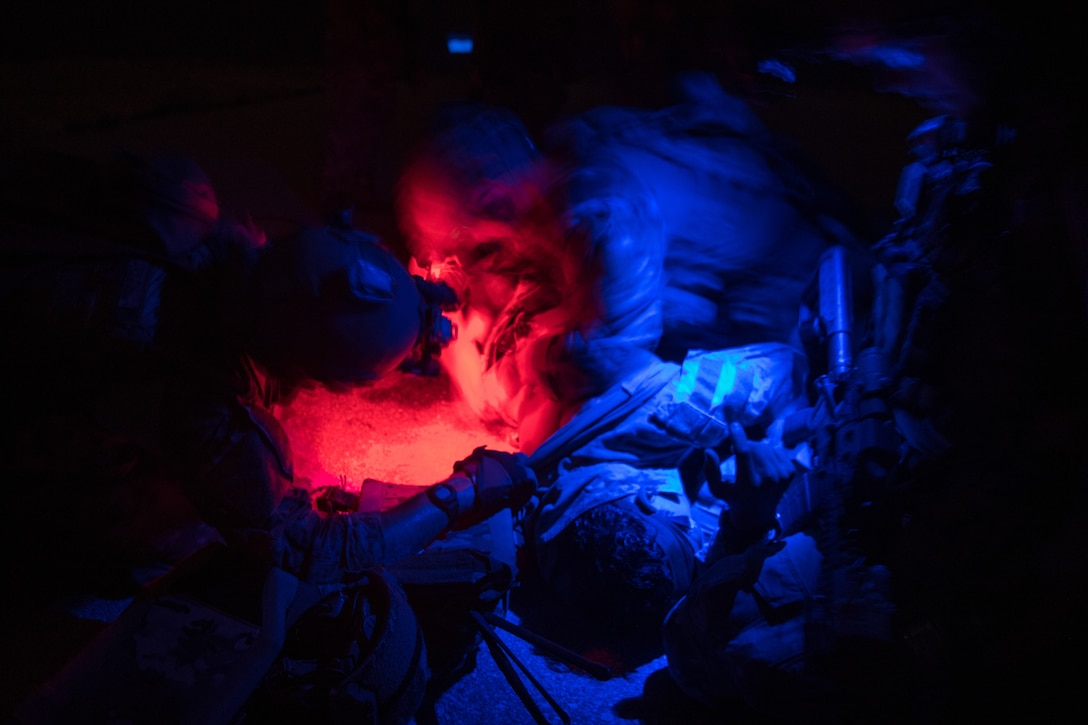 operators under a blue and red light giving care to a patient