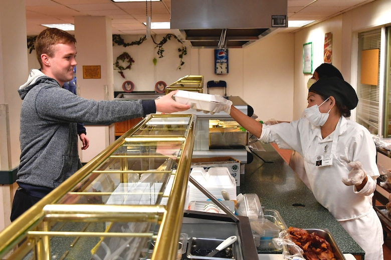 Airman 1st Class Dalton Tilt, 388th Aircraft Maintenance Squadron, is handed his lunch by Rosa Godinez, Hillcrest Dining Facility food services, at Hill Air Force Base, Utah, April 23, 2020. The food services contractor, Native Resource Development Company, Inc., is continuing to provide carry out meals for the base's Airmen during the COVID-19 pandemic while keeping the dining facility extra clean and sanitized. (U.S. Air Force photo by Todd Cromar)