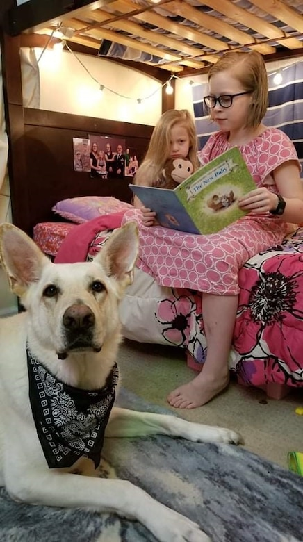 "Leo, Kirchner family dog, guards Alyssa, 10, and Isabella, 4, while reading ""The New Baby,"" Oct. 27, 2019, at their home in Virginia. The two big sisters read the book to prepare themselves for their newborn sister, Emily. (Photo by Sarah Kirchner)"