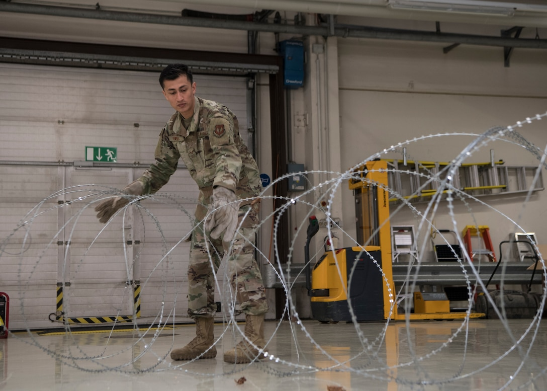 U.S. Air Force Staff Sgt. Abraham Farias, 786th Civil Engineer Squadron expeditionary engineering training manager, uncurls a roll of barbed tape at Ramstein Air Base, Germany, April 23, 2020