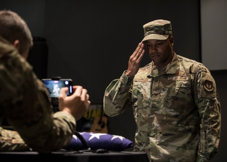 U.S. Air Force Tech. Sgt. Graeme Clouden, 786th Civil Engineer Squadron expeditionary engineering training manager, salutes a folded flag for Retired Maj. Ralph L. Turner, Tuskegee Airman, at Ramstein Air Base, Germany, April 24, 2020.