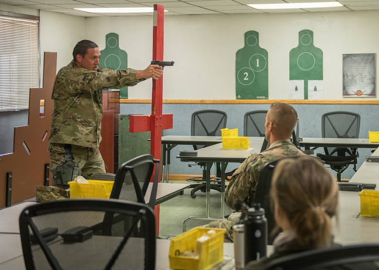 Staff Sgt. Brent Pico, 56th Security Forces Squadron Combat Arms Training and Maintenance flight instructor, demonstrates a weapon handling technique to a class April 15, 2020, at Luke Air Force Base, Ariz.