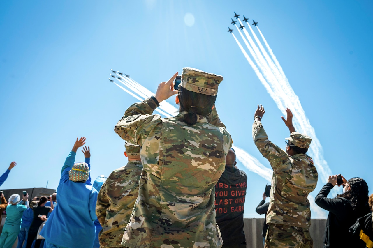 A soldier standing in a crowd of waving people wearing masks takes a photo of two jet formations flying overhead.