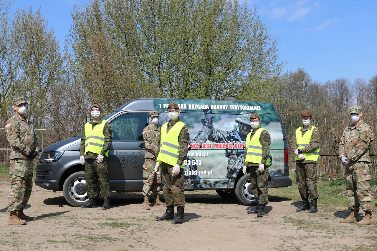 Uniformed military personnel also wearing personal protective equipment stand in front of a van.