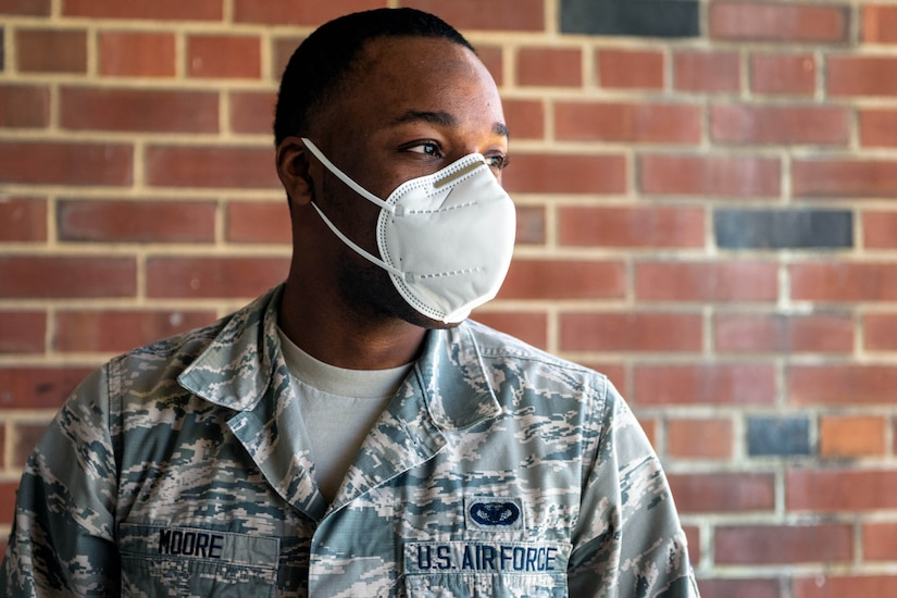 An airman wearing a mask stands in front of a building.