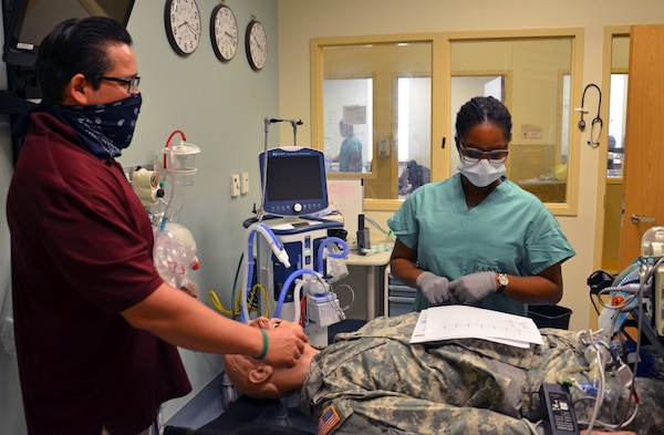 """Sgt. Jasmin Fabre, a phase 2 student and Miguel Calvillo, a phase 2 instructor in the Medical Education and Training Campus Respiratory Therapist program, review a """"patient's"""" medical information before deciding on a next course of action."""