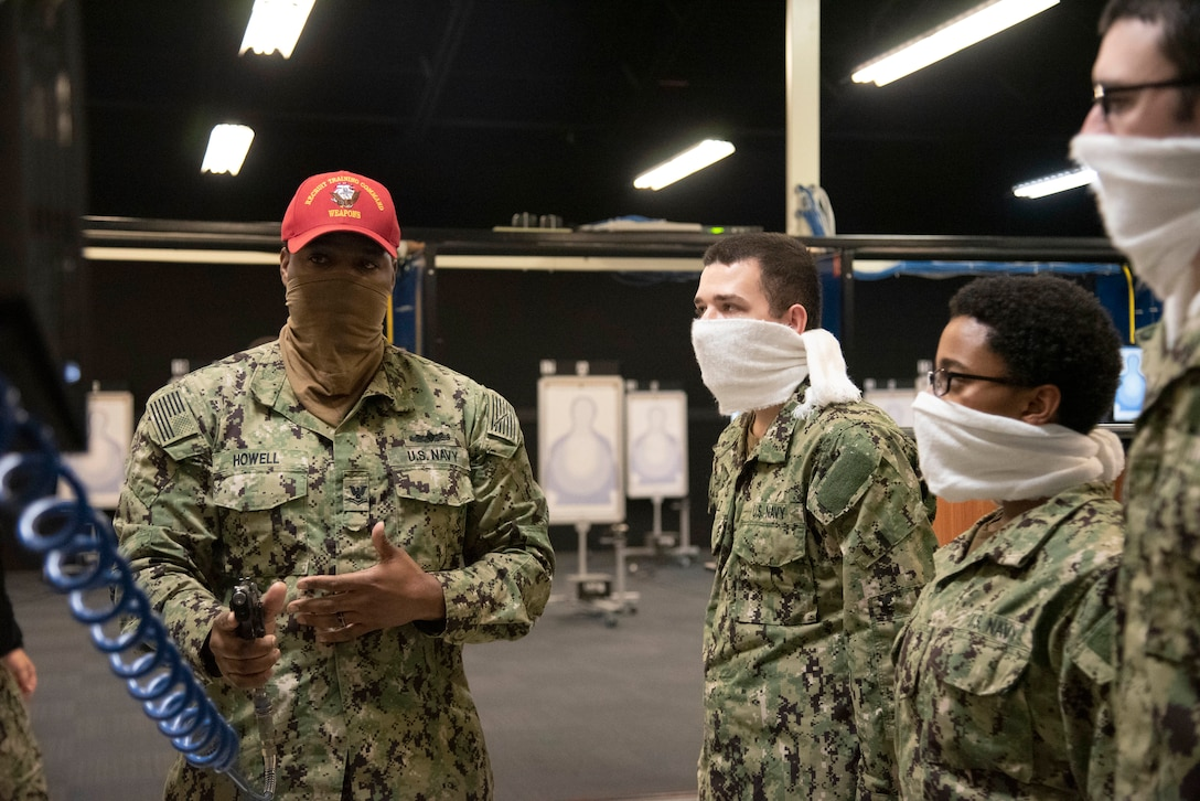 A man in military uniform and wearing a red hat talks with young military members who are standing near him. The man holds a pistol that is attached to an air hose. Everybody wears a face mask.