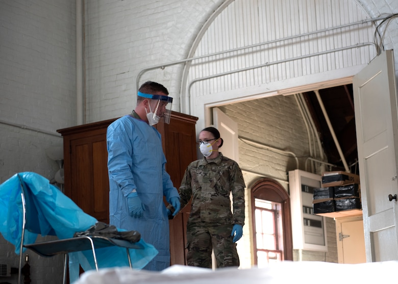 A Soldier from the Massachusetts Army National Guard Region I CBRN (Chemical, Biological, Radiological, and Nuclear) Task Force show a member of the Army Reserve how to use personal protective equipment at Tewksbury Hospital, April 21, 2020.