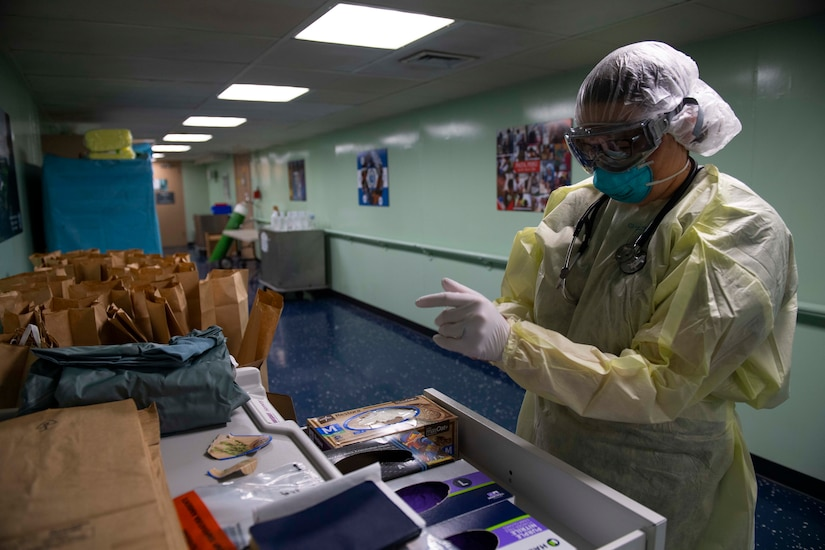 A woman puts on personal protective equipment near a table that holds dozens of paper bags.