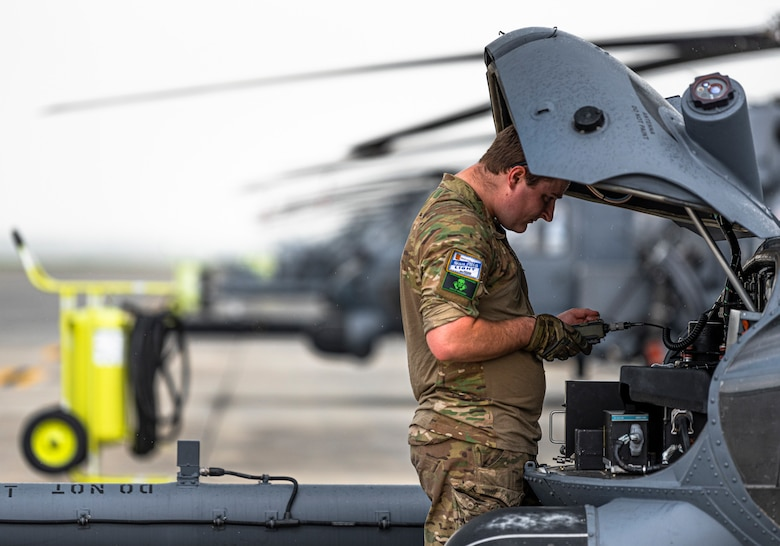 Photo of an Airman loading codes to an HH-60G Pave Hawk before a flight.