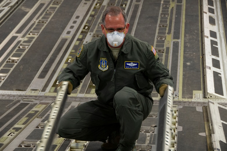 Senior Master Sgt. Robert Bertsch, a loadmaster assigned to the 446th Airlift Wing, Joint Base Lewis-McChord, Washington, flips cargo rails on the ramp of a C-17 to prepare the aircraft for a cargo upload during a local mission in late April. (Maj. Candice Allen)