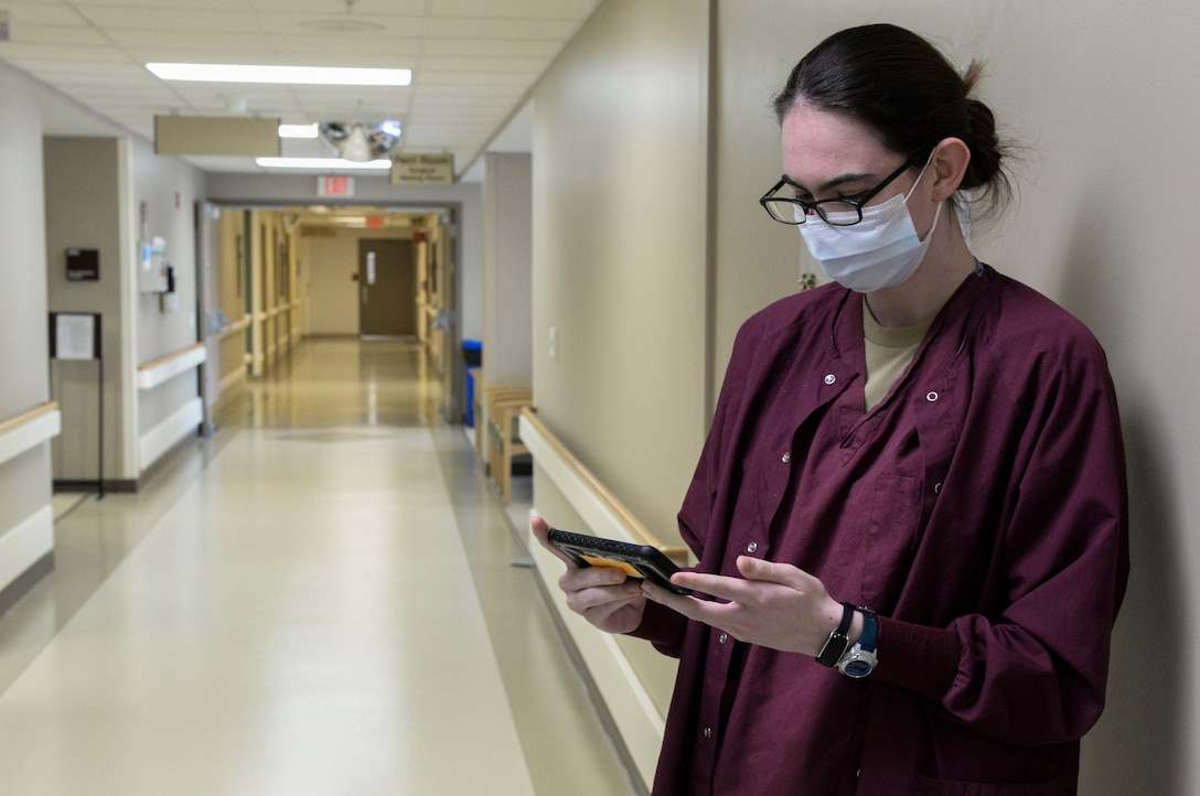 Airman 1st Class Rehanna Payne, a medical technician, uses medical monitoring technology called the Battlefield Assisted Trauma Distributed Observation Kit, or BATDOK, to check the vitals of a patient while she stands in a hallway of the Wright-Patterson Medical Center April 28. The Air Force Research Laboratory adapted this technology, originally developed for the pararescue community, for medical facilities during the COVID-19 pandemic. (U.S. Air Force photo by Wesley Farnsworth)