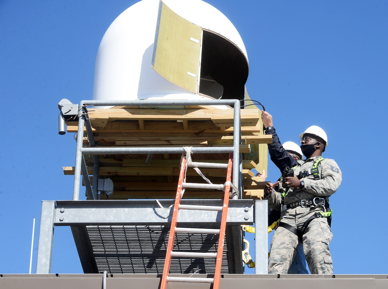 Men work on a satellite terminal.