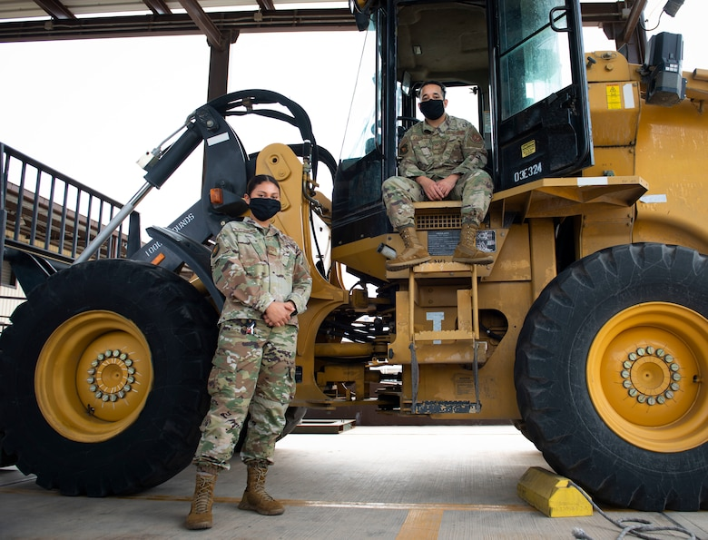 Photo of two Airmen posing by a 10K forklift