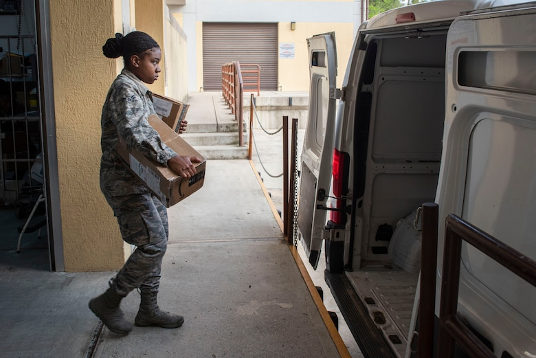 Photo of Airman loading mail into a van