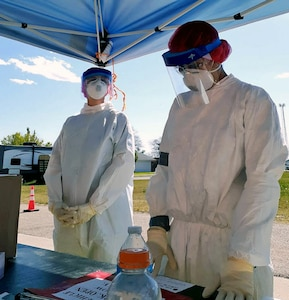 Staff Sgt. Carly Colletti (left) and Senior Airman Janie Terrazas (right), Air National Guard members with the 149th Fighter Wing, administer tests at a community-based testing facility in Friona, Texas, April 24