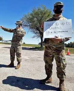 (From left) Senior Airman Josh Escarèno and Tech. Sgt. Andrew Guevara, Air National Guard members with the 149th Fighter Wing, provide test site procedures to drivers and passengers of incoming vehicles April 24, in Friona, Texas.
