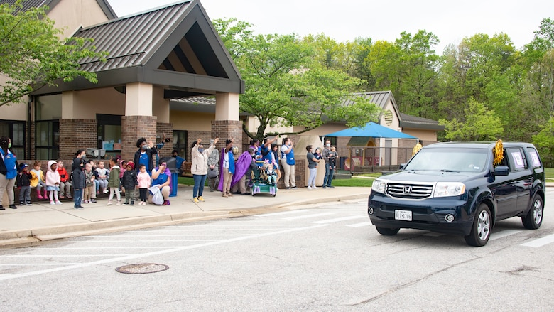 Child-care providers and children from Child Development Center 2 wave as a Month of the Military Child parade drives past on Joint Base Andrews, Md., April 24, 2020. The MotMC is an appreciation month where military families and their children are applauded for the efforts and sacrifices they make at home while their loved ones are out serving their country. (U.S. Air Force photo by Staff Sgt. Jared Duhon)