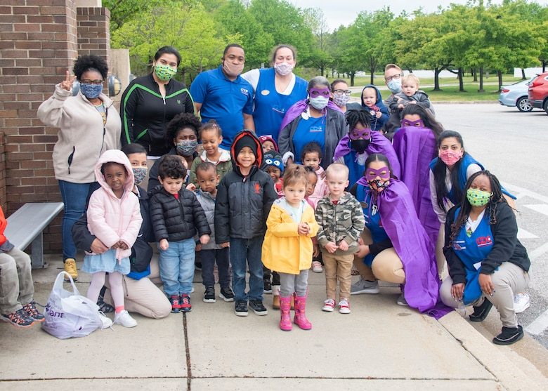 Child-care providers and children from Child Development Center 2 stand together after the Month of the Military Child parade on Joint Base Andrews, Md., April 24, 2020. Some of the providers are wearing purple as a visible way to show support and thank military youth for their strength and sacrifices. (U.S. Air Force photo by Staff Sgt. Jared Duhon)