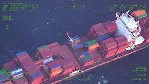 MH-60 Jayhawk helicopter hovers over a container ship