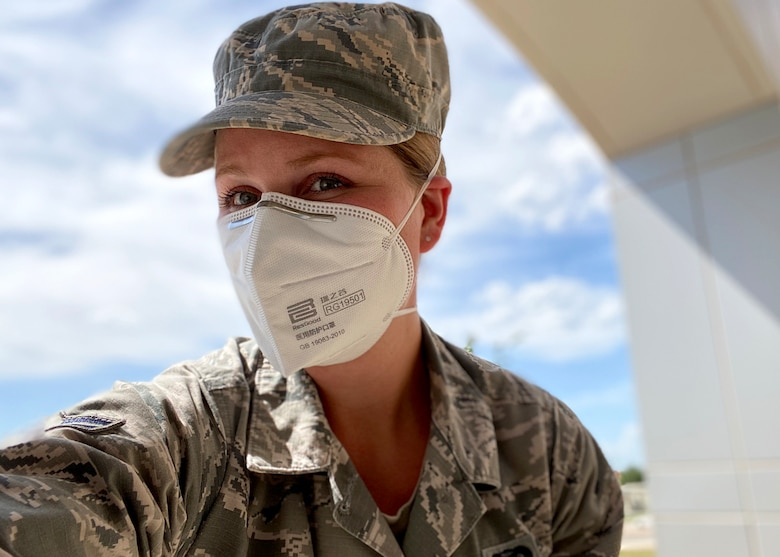 U.S. Air Force Airman 1st Class Abbey Rieves, 17th Training Wing Public Affairs photojournalist, displays her new disposable surgical mask in front of the Norma Brown building on Goodfellow Air Force Base, Texas, April 28, 2020. Rieves was the first to receive a mask from the 2,100, which were donated by San Angelo community members. (Courtesy photo)