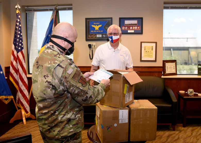 U.S. Air Force Col. Andres Nazario, 17th Training Wing commander, and San Angelo Military Advisor Group Co-Chair, Mike Boyd, unpack a donated box of disposable surgical masks inside the Norma Brown building on Goodfellow Air Force Base, Texas, April 28, 2020. Boyd and his wife delivered over 2,100 disposable surgical masks to the 17th Training Wing donated by Managing Partner of Principal LED, Bryan Vincent, and Ener-Tel Owner, Scott Wisniewski. (U.S. Air Force photo by Airman 1st Class Abbey Rieves)