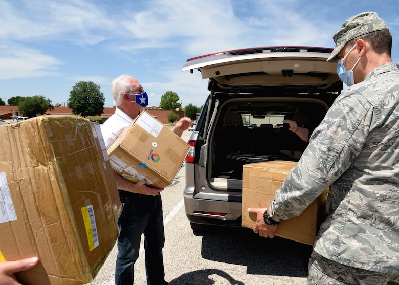 San Angelo Military Advisor Group Co-Chair, Mike Boyd, and U.S. Air Force Airmen from the 17th Training Wing unpack boxes of disposable surgical masks in front of the Norma Brown building on Goodfellow Air Force Base, Texas, April 28, 2020. The masks donated were a token of appreciation and demonstrate the tight-knit bond between the San Angelo Community and Goodfellow. (U.S. Air Force photo by Airman 1st Class Abbey Rieves)
