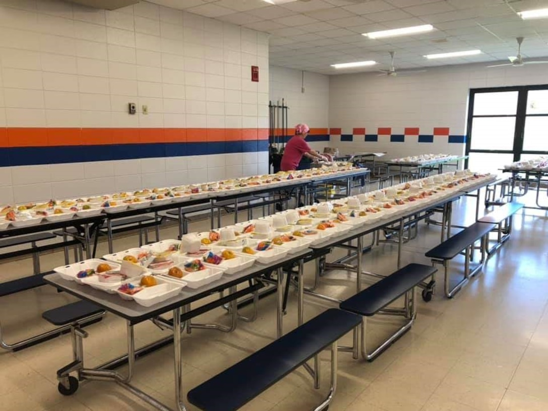 Tables in a school cafeteria are filled with pre-made boxed lunches.