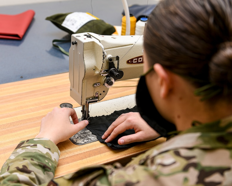 Airman with hands at a sewing machine.